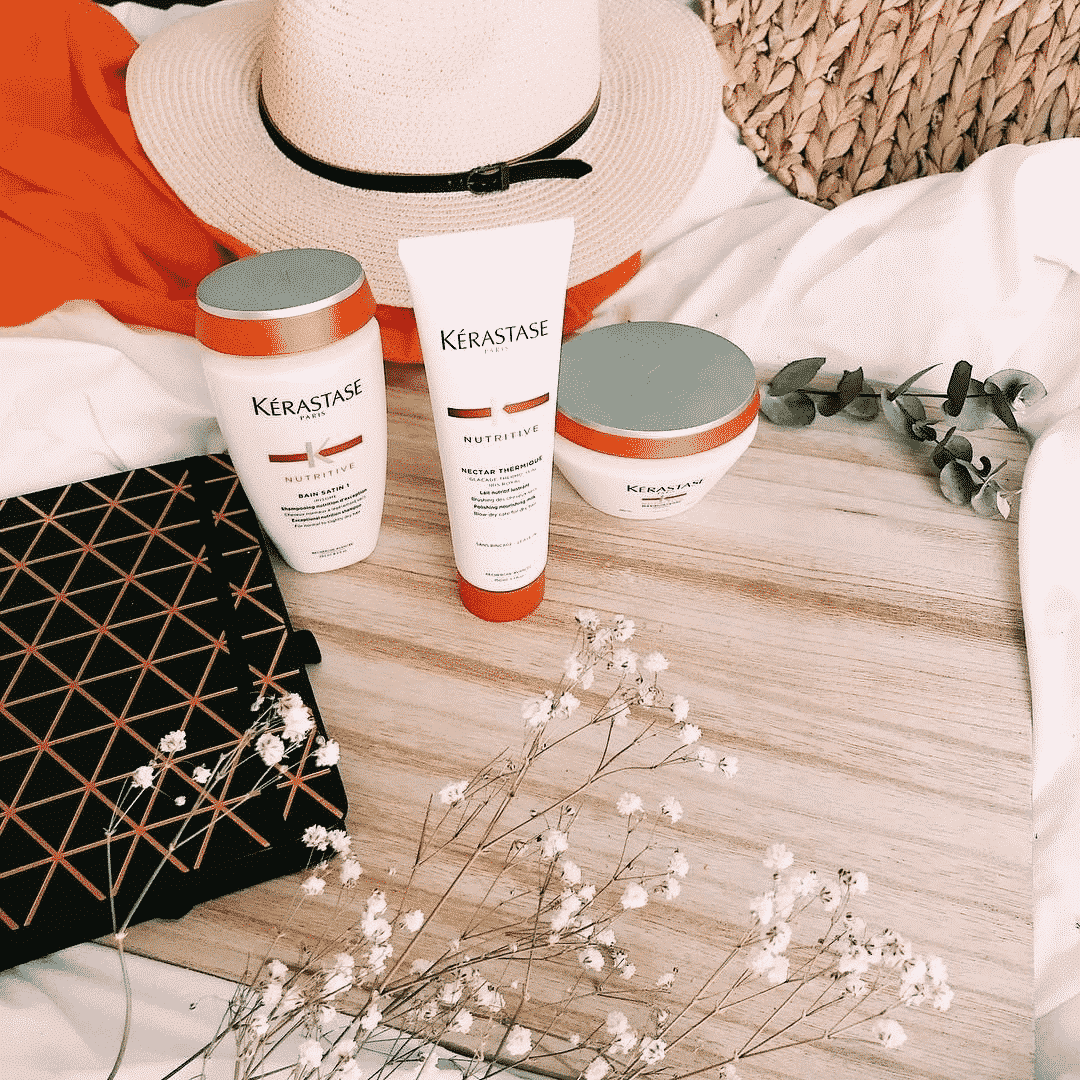 Kerastase nutritive beauty products on a wooden table with flowers a sunhat towels and a binder