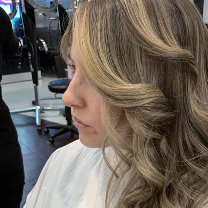 woman with blonde curly hair sitting at a hair salon