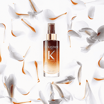 Kerastase nutritive night serum bottle surrounded by whie and orange flower petals