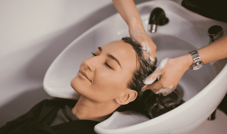 smiling woman getting her hair washed at a hair salon