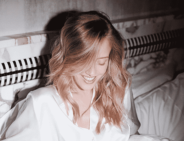 smiling blonde woman wearing white in bed