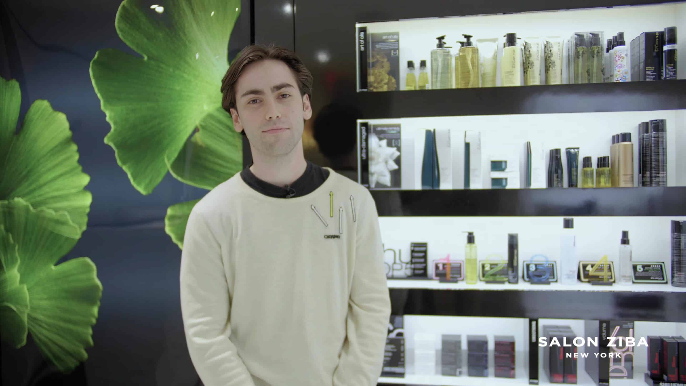 Smiling man in a white sweater standing in front of hair products
