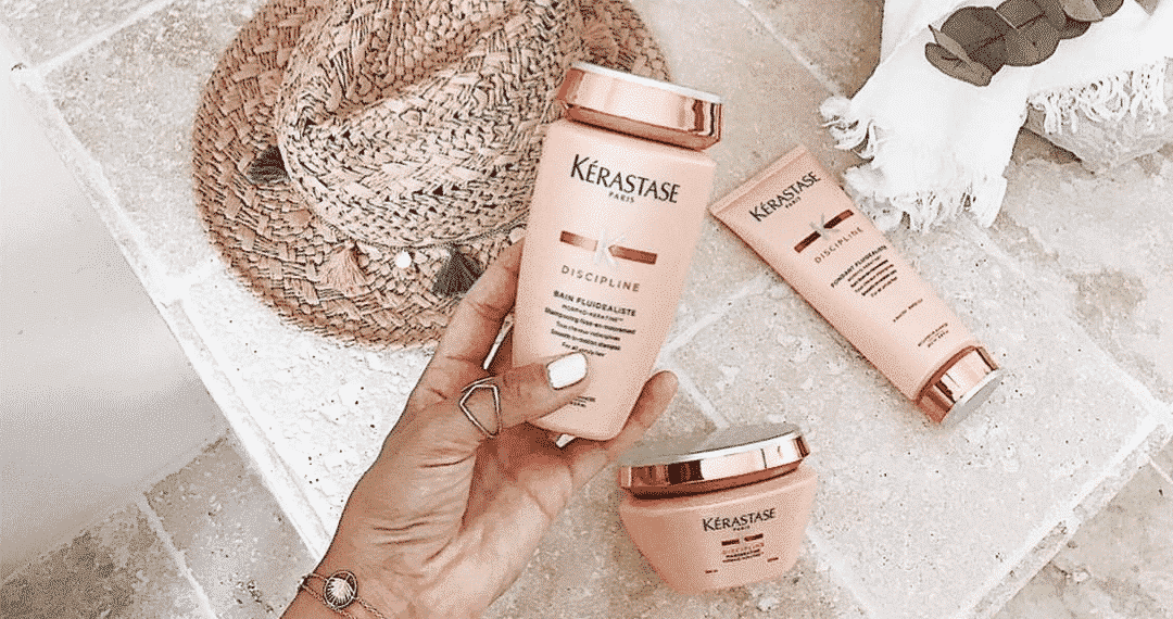 hand with white nails holding a kerastase discipline hair product