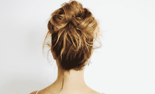 back picture of a brown haired woman with her hair up in a messy bun