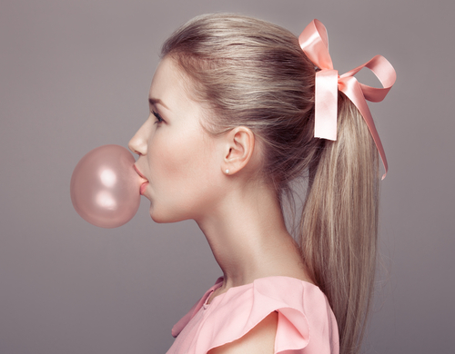 sideways profile of a woman in a pink dress with a pink bow blowing a pink bubble gum