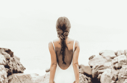 woman in white one piece with a braid facing away from the camera in rocky background