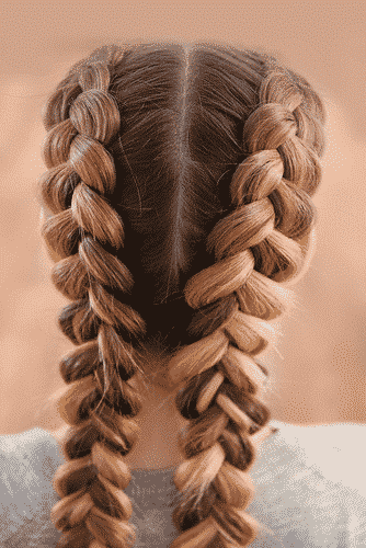 back view of a brown haired woman with two french braids