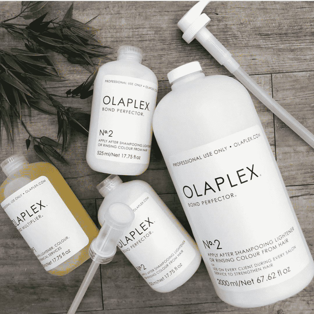 white olaplex bottles placed on a wooden table with plant leaves