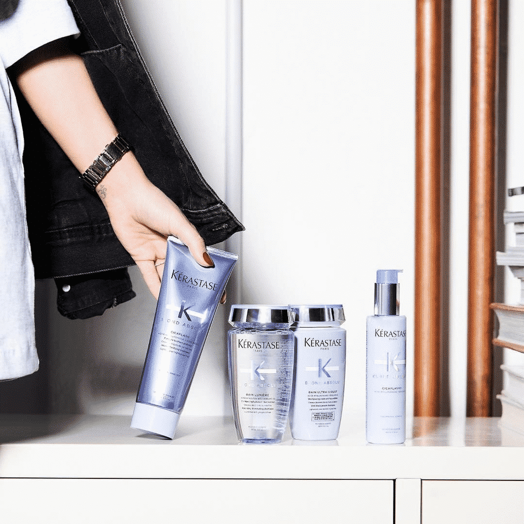 woman's hand picking up kerastase product from a white shelf