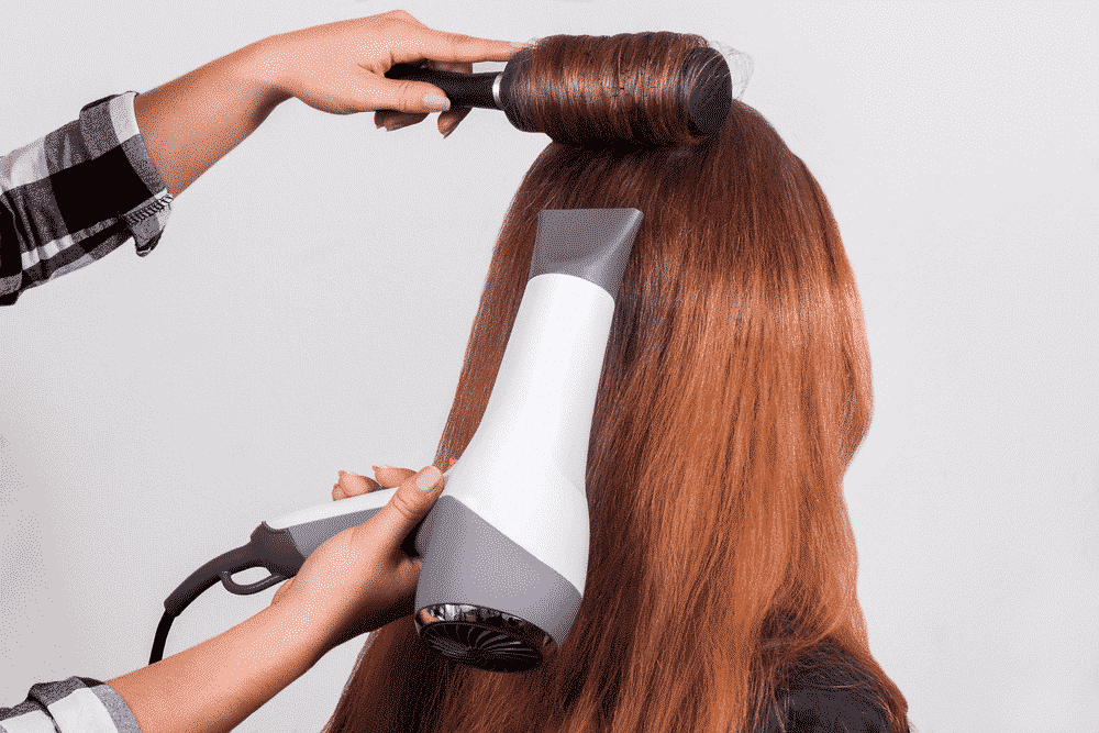 hair stylist blowdrying light brown hair while rolling it with a round brush