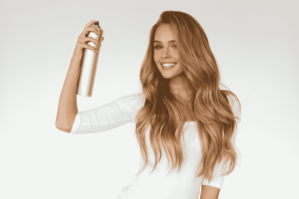 blonde woman in a white slim top with long sleeves holding a grey can of hair spray while smiling