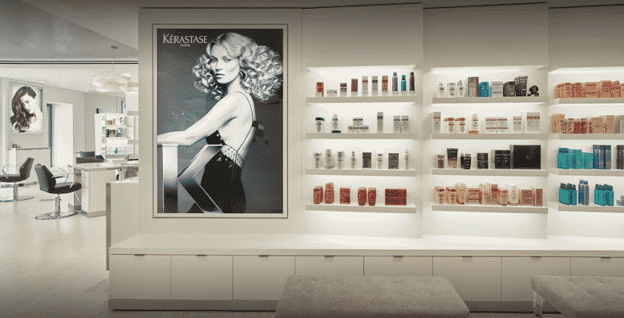luxurious hair salon with white walls, bright lights, a black and white poster of a woman with curly hair and rows of hair products on lit shelves