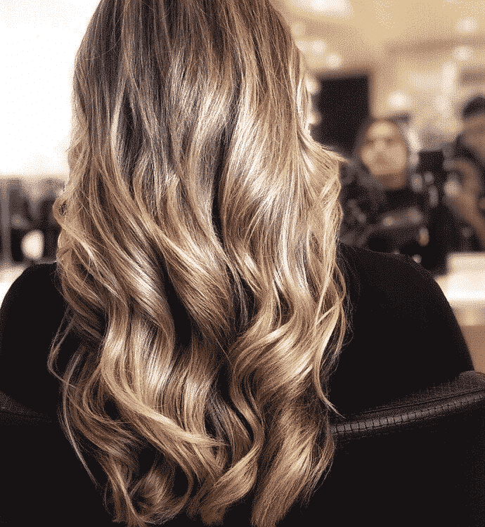 woman with brown highlights sitting in a hair salon