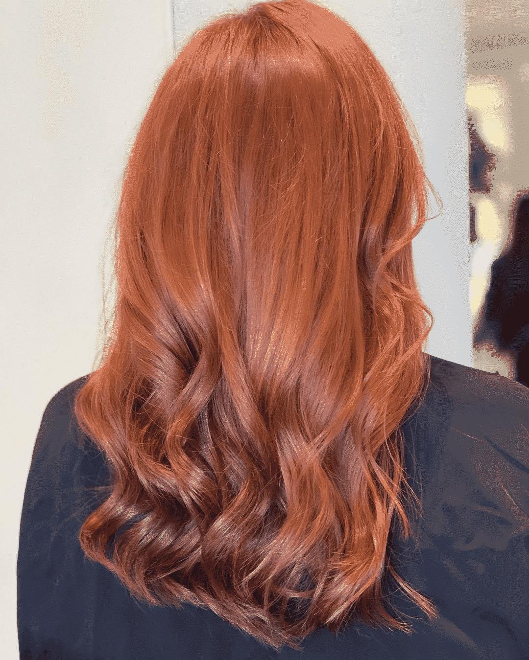 woman with auburn dyed hair sitting back in a hair salon