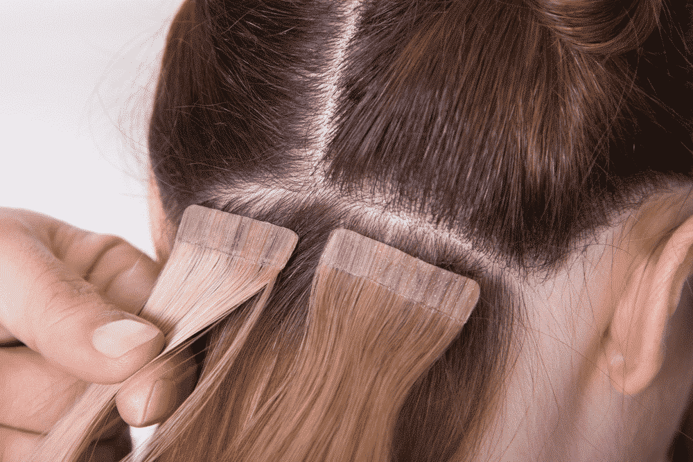 light colored extensions being applied to brown hair