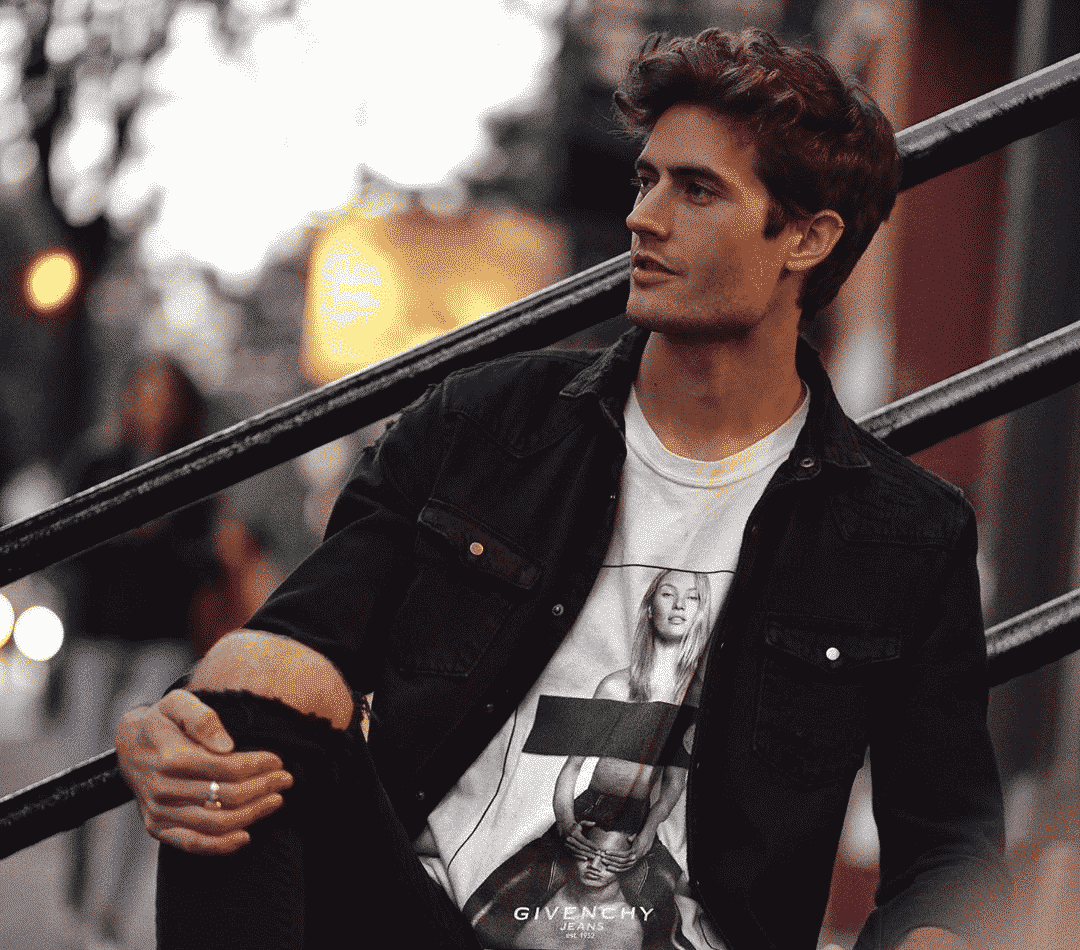 good looking young guy with brown hair wearing a light black jacket and a white t shirt sitting against a railing on an outside staircase