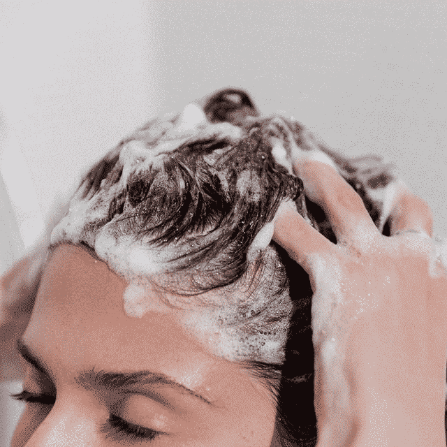 woman shampooing hair with eyes closed