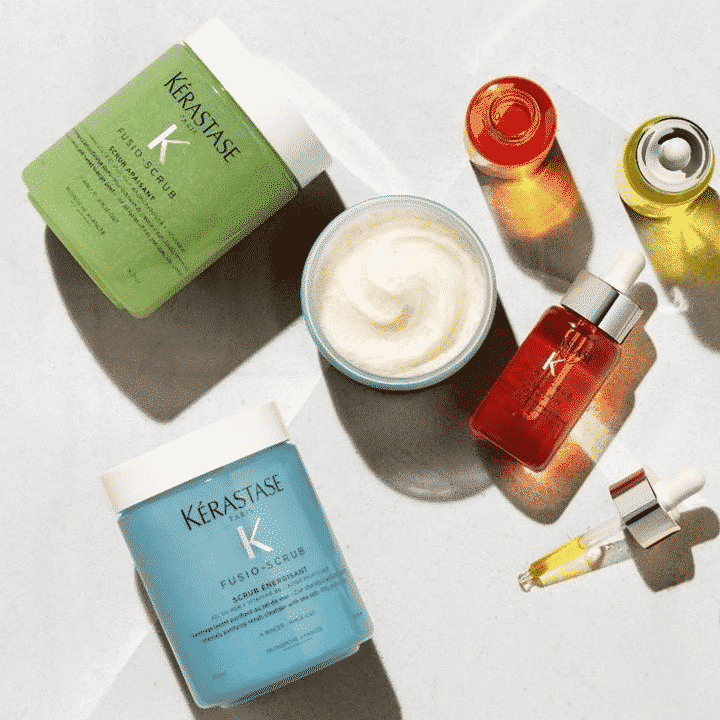 kerastase fusio scrub products and colorful bottles scattered on a table