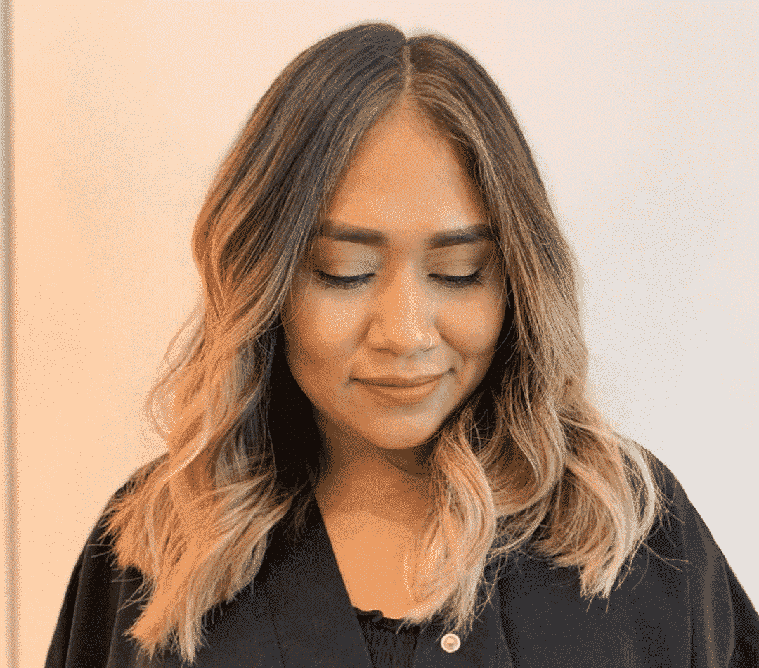 asian woman with bright balayage looking down with a smile while wearing a hair salon scrub