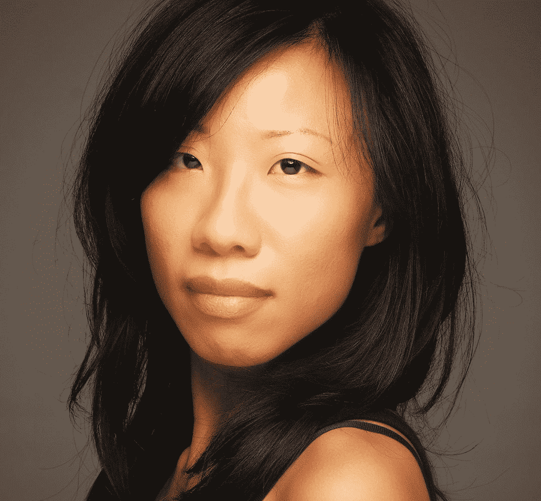 asian woman with black natural hair looking sideways at the camera