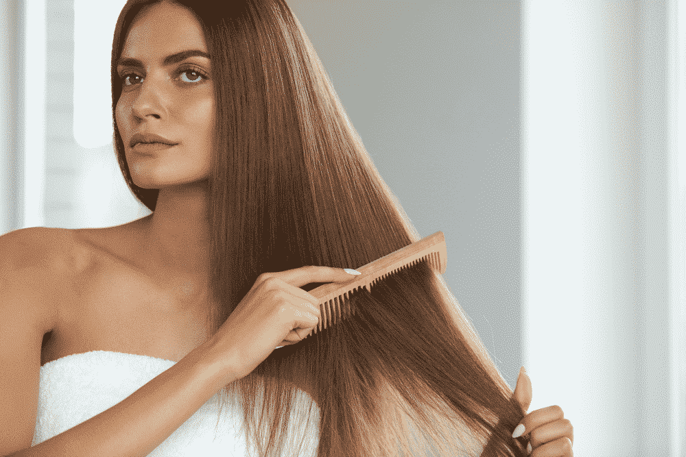 woman with long brown hair wrapped in a white towel and brushing the hair with a beige comb