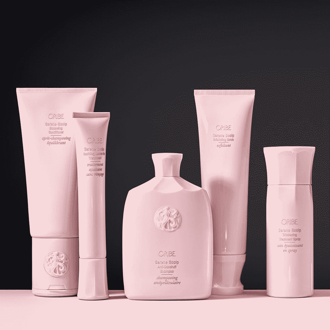 full line of oribe products in pink bottles in front of a black background