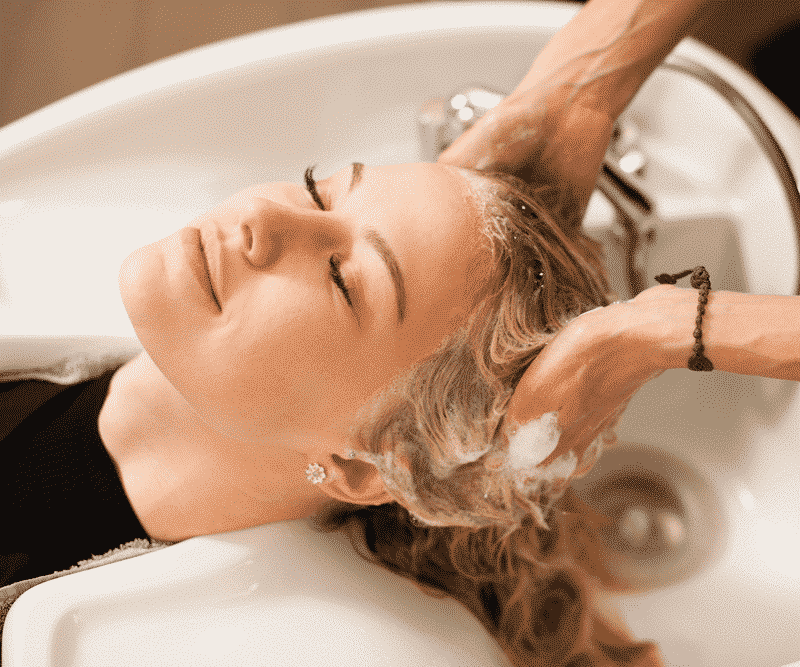woman in a black shirt getting her hair washed by a hair dresser's hands
