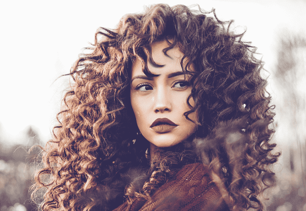 curly haired woman with brown locks and dark lipstick wearing a burgundy sweater