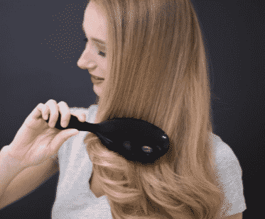 blonde woman with wavy hair brushing it with a black round brush