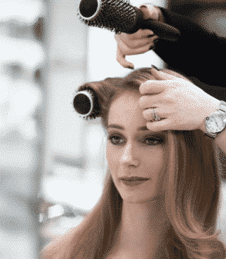 woman with long brown locks getting her hair curled