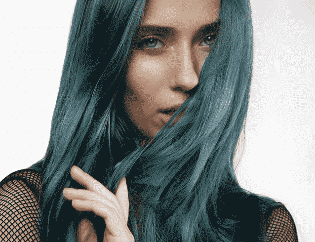 young woman with grey blue hair holding it in front of her face