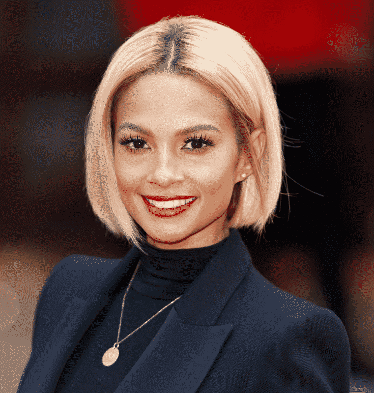 smiling woman in a black turtleneck and a black blazer with a golden pendant around her neck and a blonde bob haircut