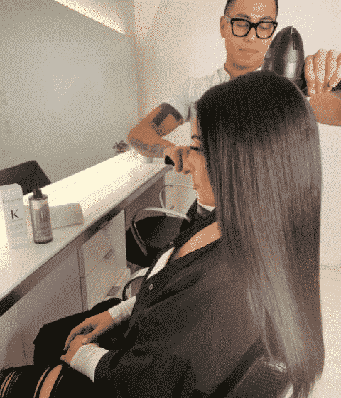 woman with long black hair sitting in a hair salon while stylist blow dries