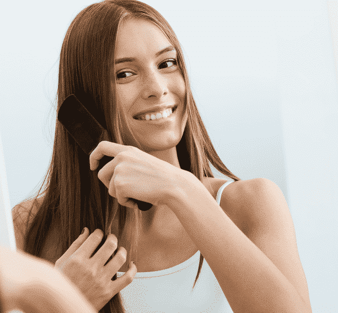 happy woman in a white top brushing her brown hair with a long brush