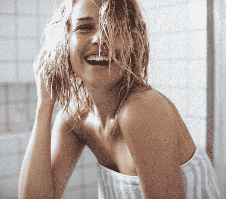 blonde woman with short wet hair laughing in the bathroom wrapped in a towel