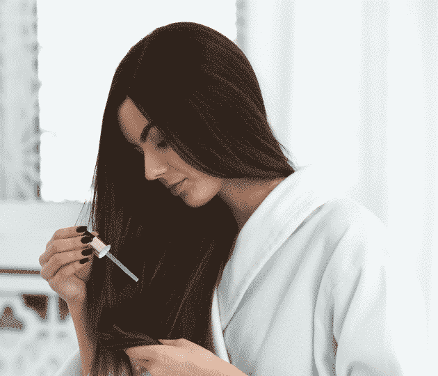 woman in a bathrobe applying oil to long brown hair